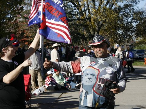 """Trump supporter Randall Thom stands with a """"Make America Great Again"""" flag outside Zorn Arena."""