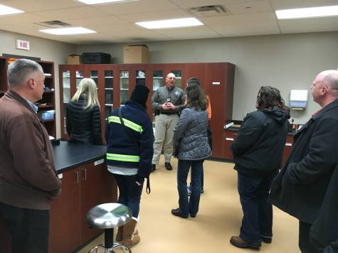 Detective Don Henning showing participants of the academy the inspection room where police take crime scene evidence to be analyzed by professional examiners.