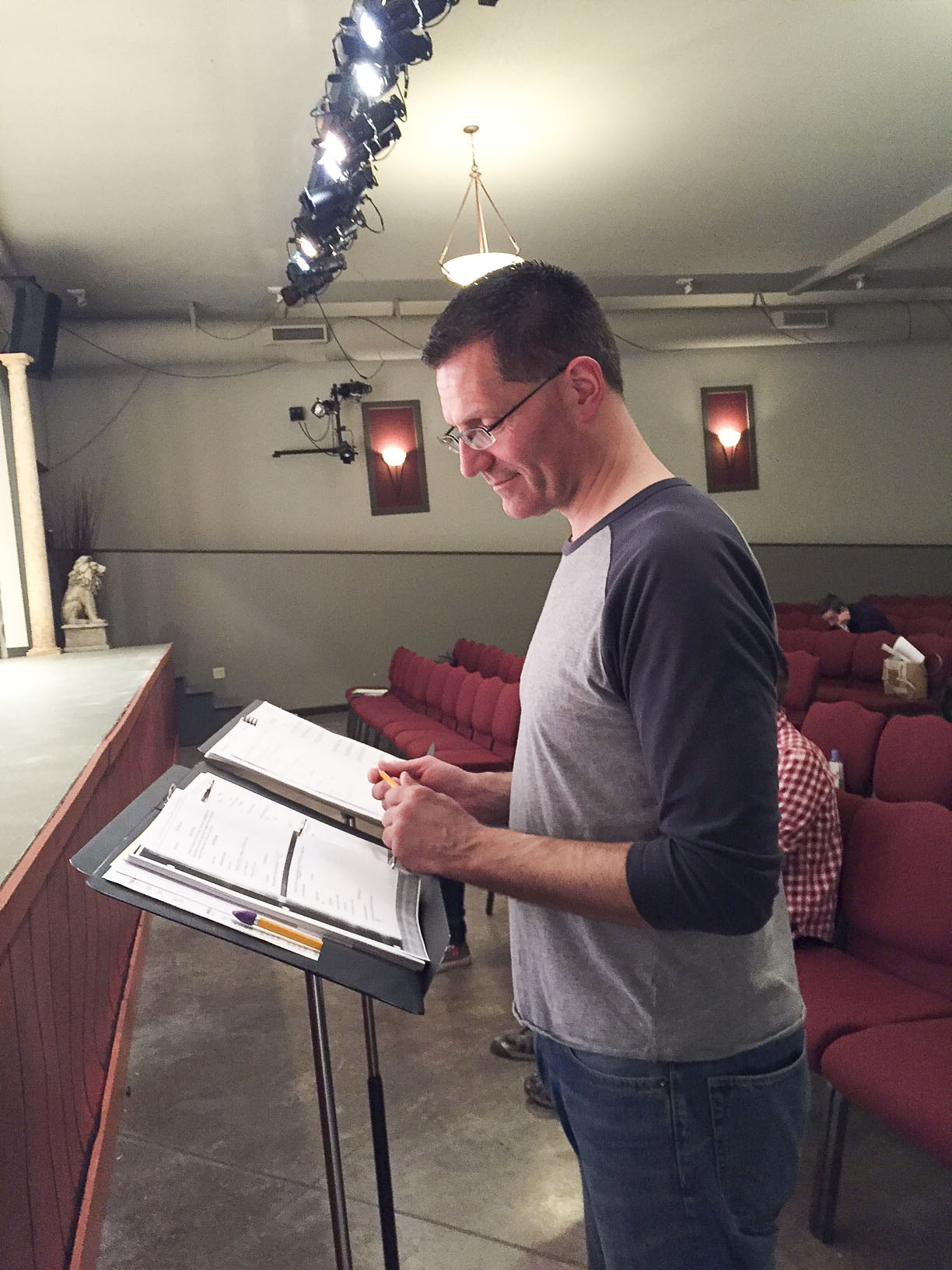 Wayne Marek looks over the A Funny Thing Happened On The Way To The Forum script and gives out direction to actors on stage.