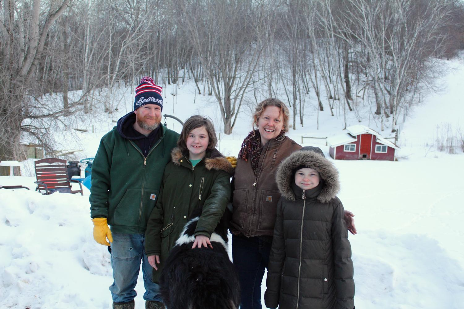 Andy and Stephanie Schneider, owners of Together Farms, pose for a photo with their two daughters, Madelynne, 11, right and Adeyle, 8, left, and their dog Mr. Fluffypants, on Feb. 12. The family moved to their Mondovi farm in 2009.