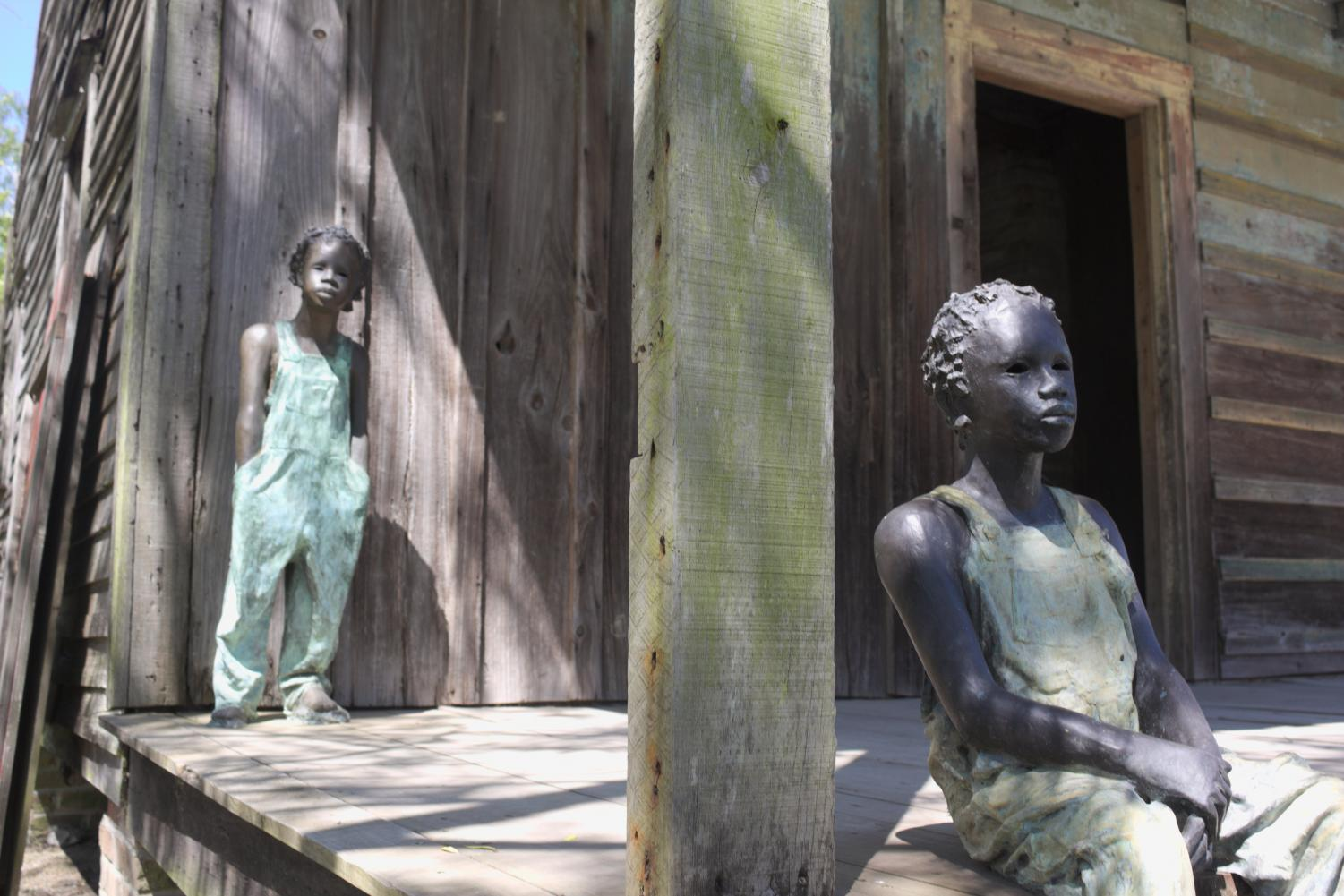 Statues resembling children born into slavery overlook Whitney Plantation from the porch of the slave quarters they once lived in. ©2018 Max Perrenoud
