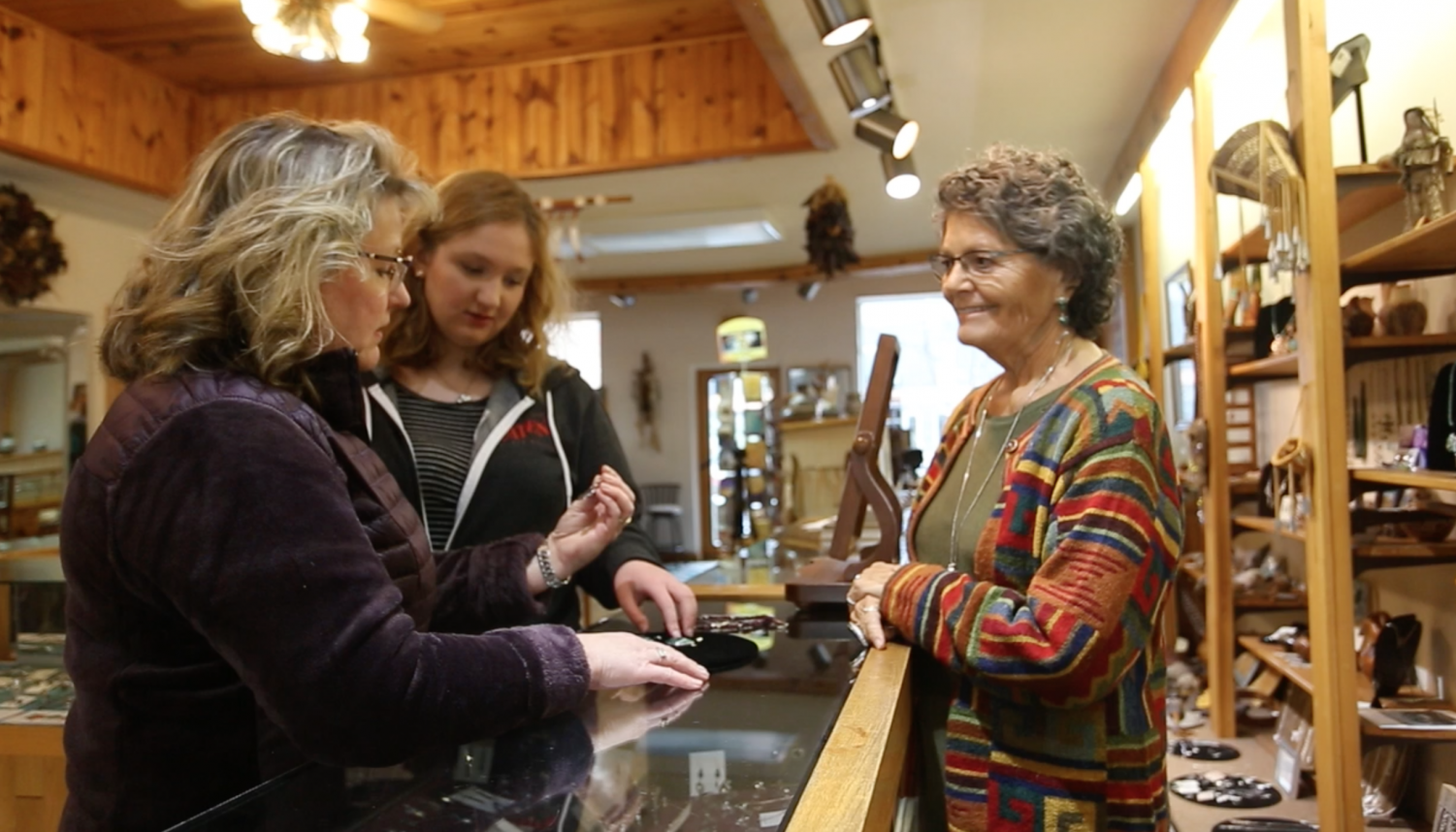 Jane Wolf guides her customers in choosing jewelry at the Silver Feather. © 2018 Xin Tao