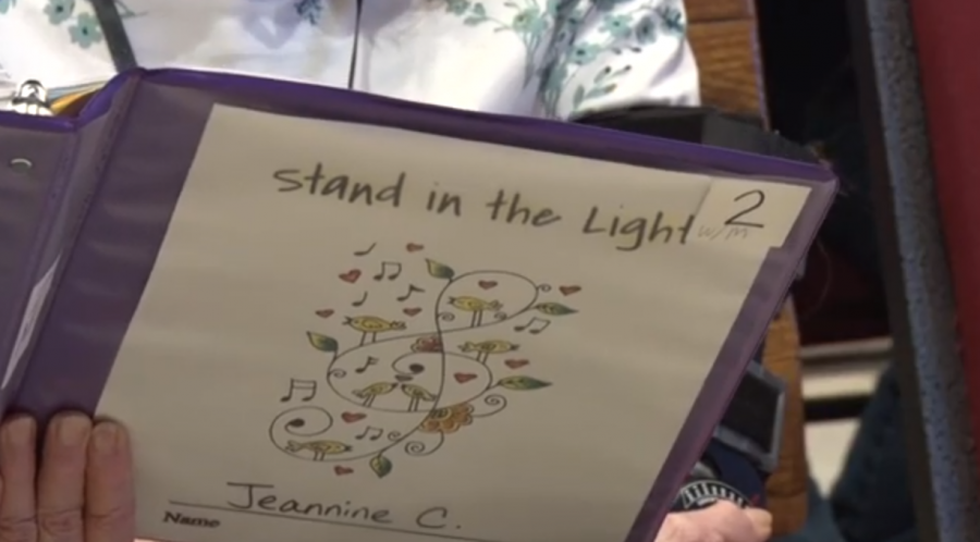 The+Stand+in+the+Light+Choir+uses+their+color-coded+binders+to+practice+for+their+upcoming+concert.+