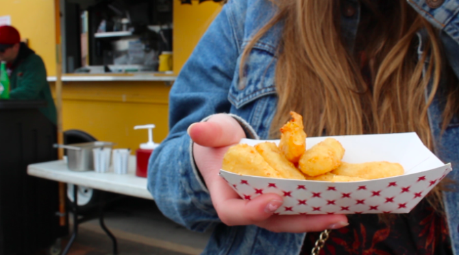 An+attendee+eats+cheese+curds+outside+of+The+Hubb+at+Food+Truck+Friday.%0A